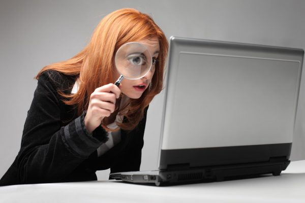 Woman-with-magnifying-glass-looking-at-computer-1678-x-1119-px